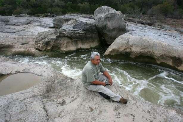 Carlos Hernandez of Johnson City takes advantage of good fishing conditions amid the rocks.