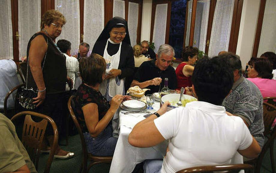 An unidentified nun serves dinner for pilgrims in Casa Mater Mundi. Photo: ALESSANDRA TARANTINO, Associated Press