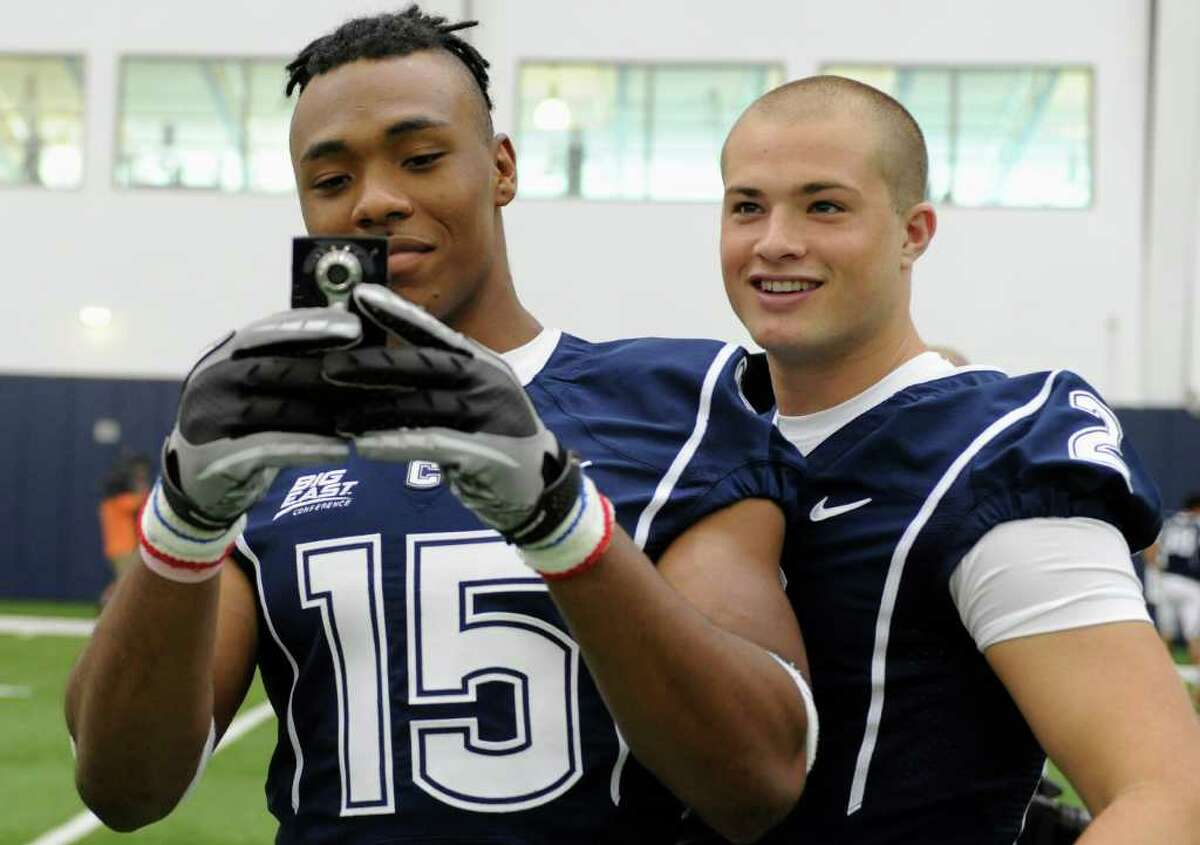 Connecticut's Jerome Junior, left, takes a photo of the media as teammate Michael Nebrich, right, looks on, during the NCAA college football team's media day in Storrs, Conn., Friday, Aug. 12, 2011. (AP Photo/Jessica Hill)