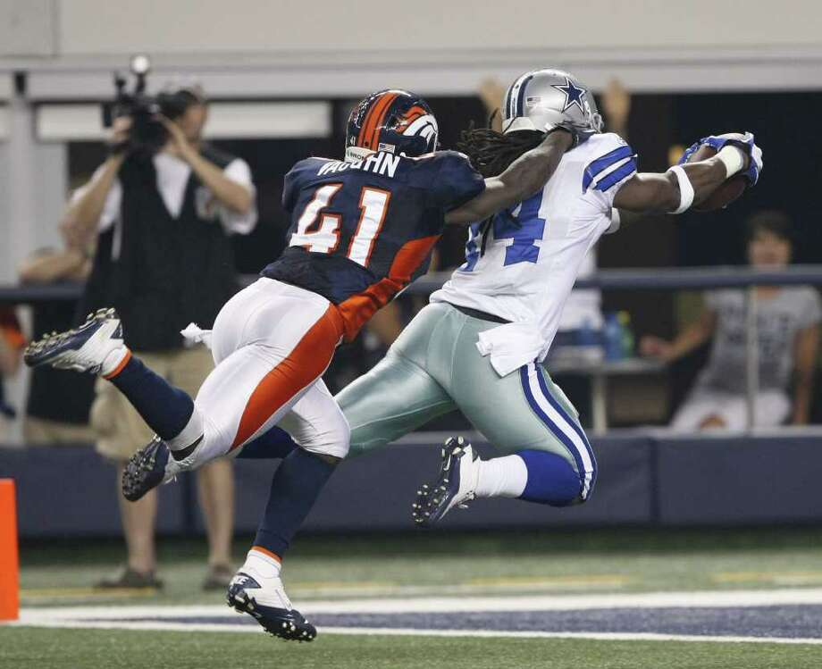 Dallas Cowboys wide receiver Dwayne Harris (14) leaps into the endzone to makes a 76-yard touchdown, while tackled by Denver Broncos cornerback Cassius Vaughn (41)  during the second half of a preseason NFL football game Thursday, Aug. 11, 2011, in Arlington, Texas. (AP Photo/Waco Tribune Herald - Jose Yau) Photo: Jose Yau, MBO / Waco Tribune Herald 2011