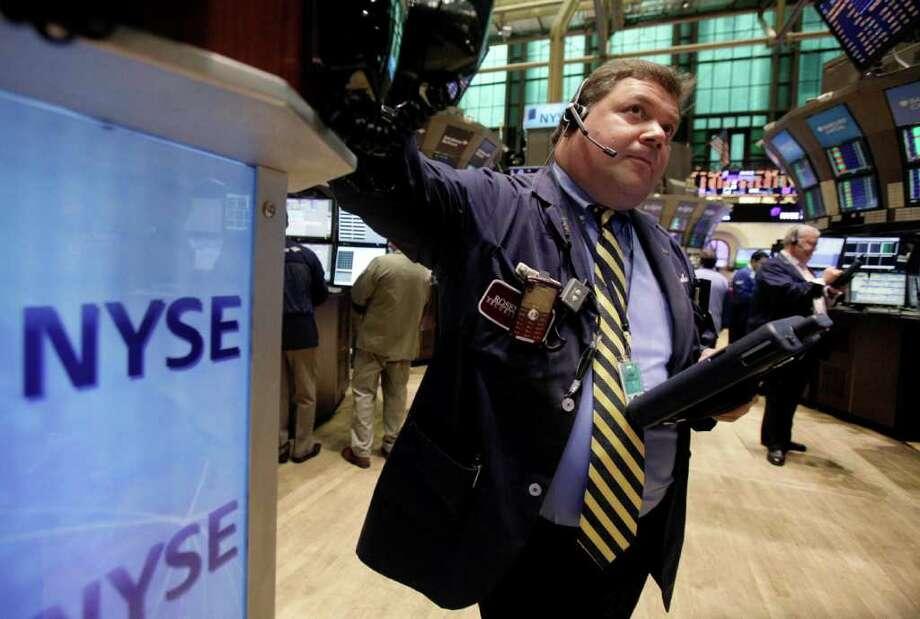 John Santiago works on the floor of the New York Stock Exchange Friday, Aug. 12, 2011. (AP Photo/Richard Drew) Photo: Richard Drew