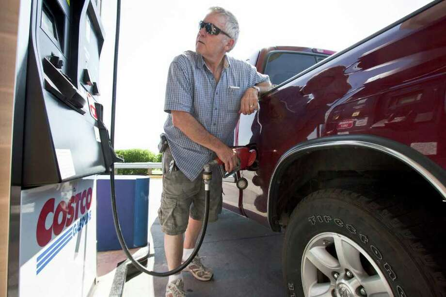 In this Aug. 9, 2011 photo, Gary Hartwig of Gretna, Neb., fuels his car at a Costco gas station in Omaha, Neb. Consumers spent more on autos, furniture and gasoline in July, pushing up retail sales by the largest amount in four months. The gain could signal that Americans are a little more confident and help dispell fears that the country is in danger of toppling into another recession. (AP Photo/Nati Harnik) Photo: Nati Harnik