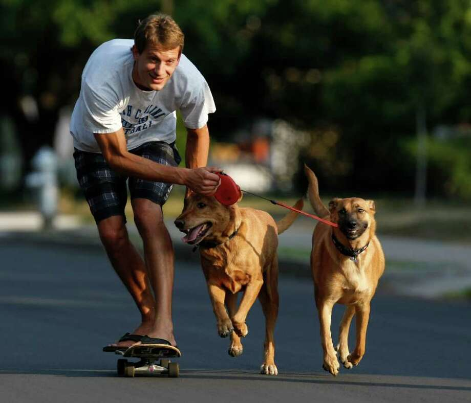 Whit Pharr's dogs, Lola (right) and Haden pull him on a skateboard, something Pharr says they do every evening. Photo: KEVIN MARTIN, KEVIN MARTIN/kmartin@express-news.net / SAN ANTONIO EXPRESS-NEWS