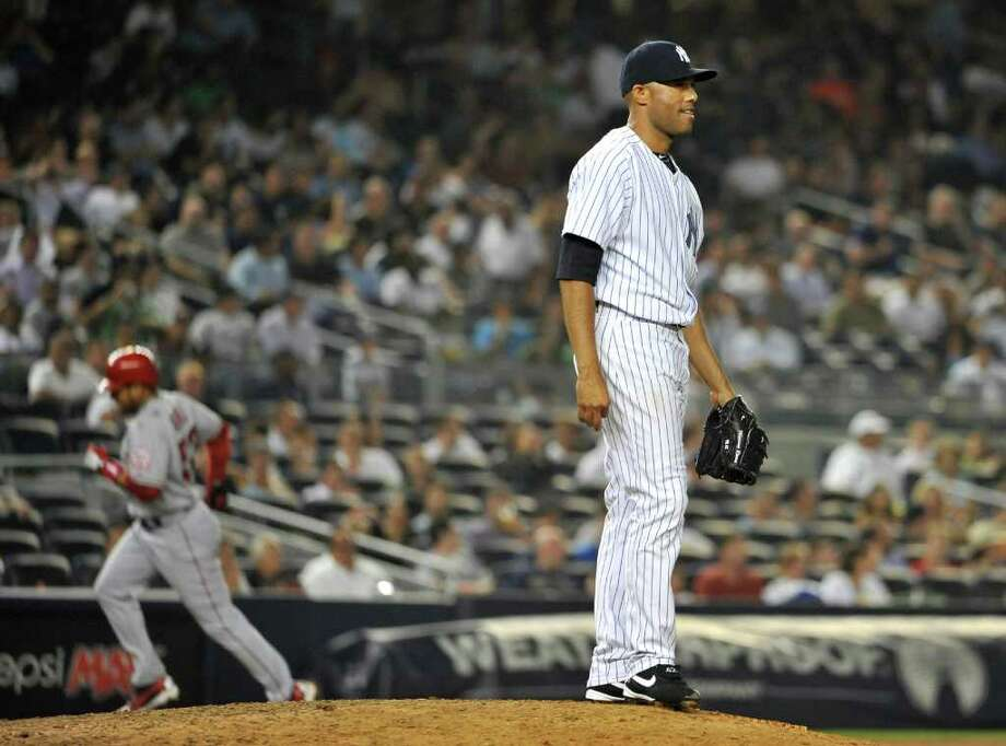 New York Yankees' Mariano Rivera stands on the mound as Los Angeles Angels' Bobby Abreu rounds third base after hitting a two-run home run in the ninth inning of a baseball game on Tuesday, Aug. 9, 2011 at Yankee Stadium in New York. Abreu hit two home runs during the Angels' 6-4 win. (AP Photo/Kathy Kmonicek) Photo: Kathy Kmonicek