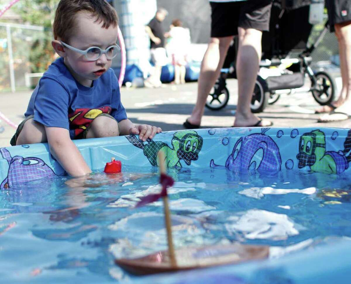 Jay Matthew, 3, plays with his own handmade toy boat at the South Lake Union Block Party on Denny Way and Westlake Avenue in Seattle on Friday, August 12, 2011.