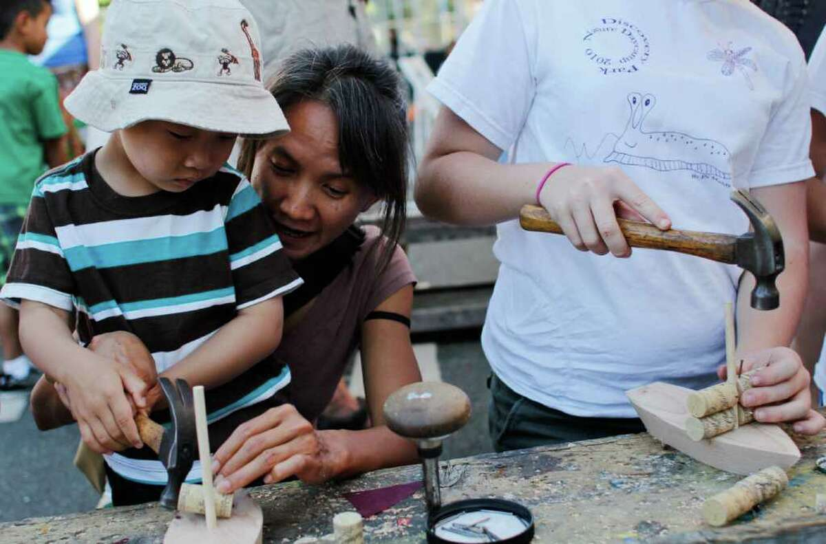 Phi Nguyen and her nephew Miles Nguyen build a wooden boat.