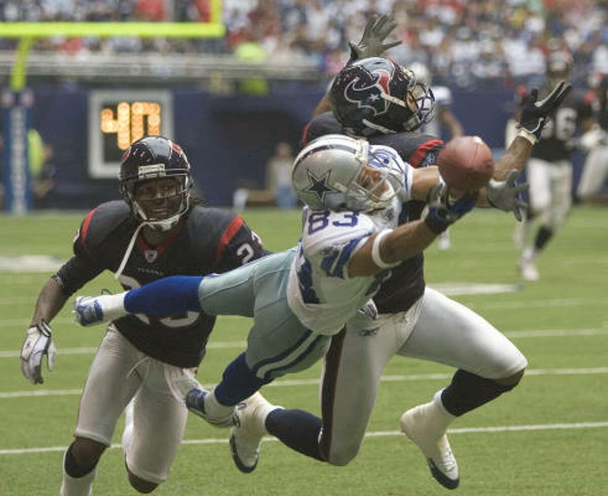 Cowboys receiver Terry Glenn stretches for a pass behind Texans cornerback Dunta Robinson.