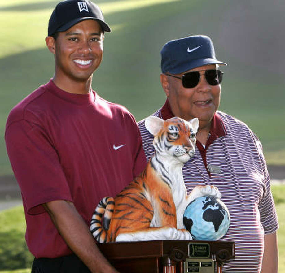 Tiger Woods celebrates with his father Earl Woods after winning the sixth annual Target World Challenge golf tournament at Sherwood Country Club in Thousand Oaks, Calif., on Dec. 12, 2004. Photo: LUCY NICHOLSON, REUTERS