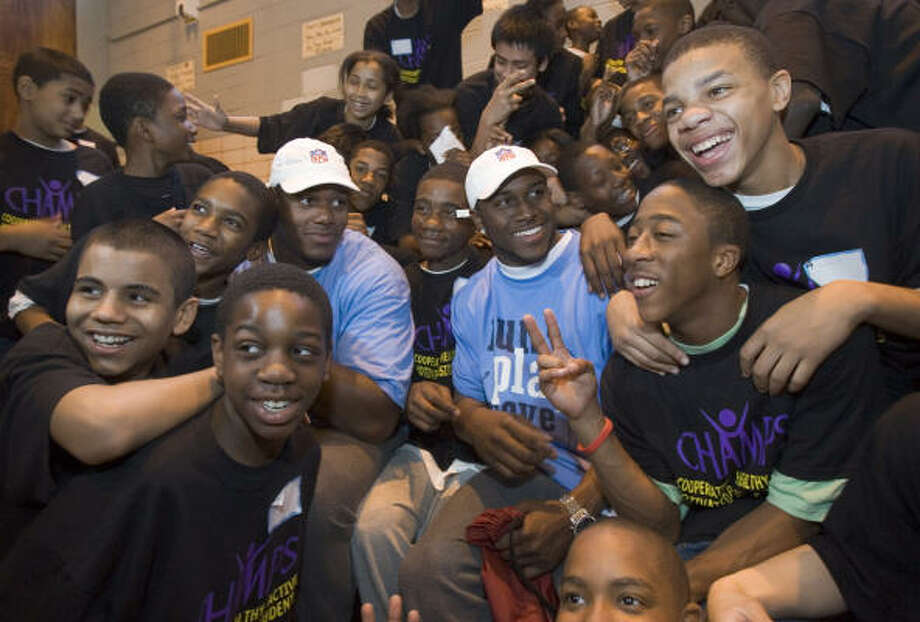 Reggie Bush, center right, former running back from USC, and D'Brickashaw Ferguson, offensive tackle out of Virginia, sit in the middle of several students from Junior High School No. 13 Thursday in New York. Photo: BRETT COOMER, CHRONICLE