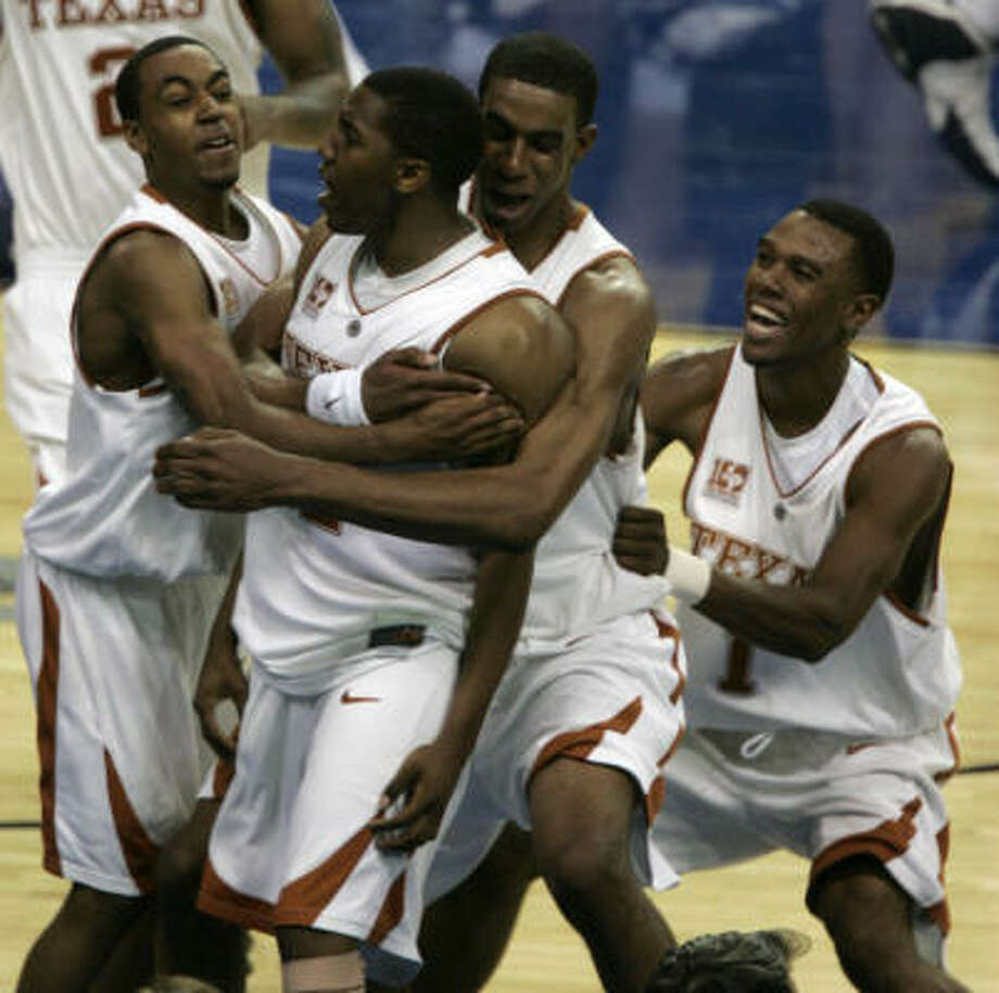 Texas' Kenton Paulino (12) is mobbed by his teammates after hitting a last-second shot to beat West Virginia 74-71 in the Atlanta Regional semifinal Thursday night. Photo: BRETT COOMER, CHRONICLE