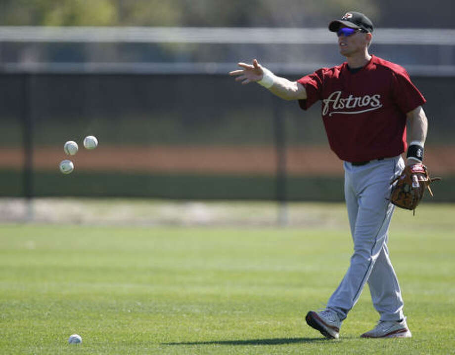 Craig Biggio throws the baseballs in a pile after shagging them during batting practice at the Astros' spring training facility on Wednesday. Photo: KAREN WARREN, CHRONICLE