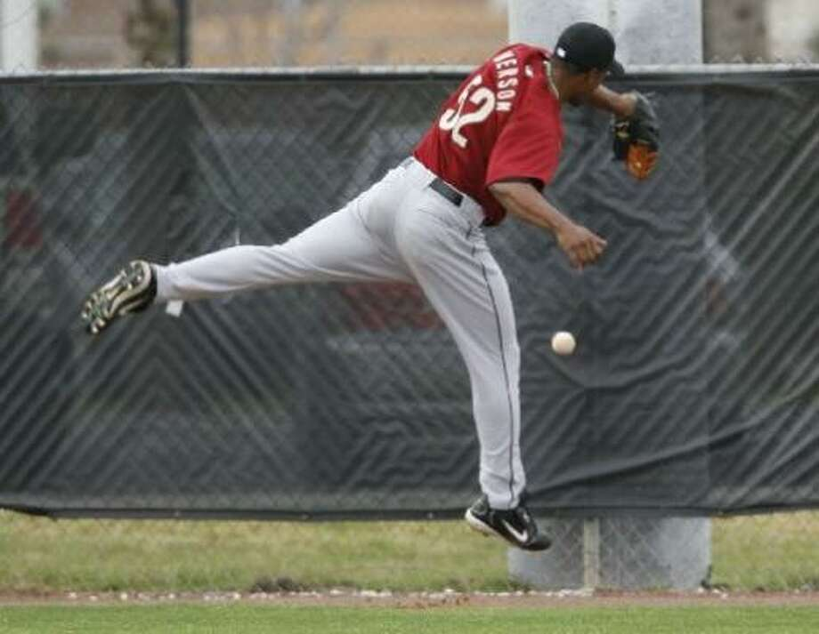 Charlton Jimerson leaps against the wall for a ball in the outfield during workouts at the Astros' spring training facilities on Sunday. Photo: Karen Warren, Chronicle