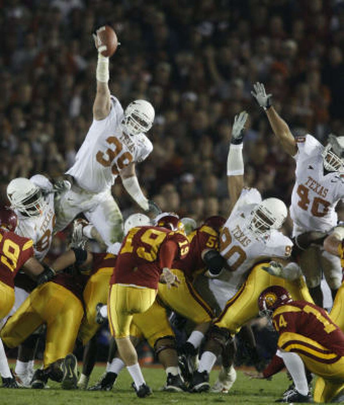 Trojan place kicker Mario Danelo gets the ball by the outstretched arm of Texas special teams player Brian Robison during the second quarter of the Rose Bowl game in Pasadena, Calif., Wednesday.