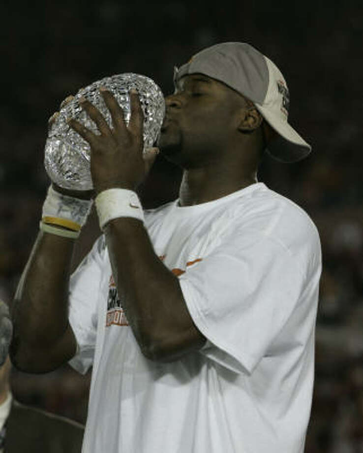 Texas' Vince Young kisses the championship trophy after the Longhorns defeated USC 41-38 in the BCS Championship Game in 2006. Where does that game rank among college football's championship games? Click through the gallery for our list of the best and worst since 1998. Photo: BRETT COOMER, CHRONICLE