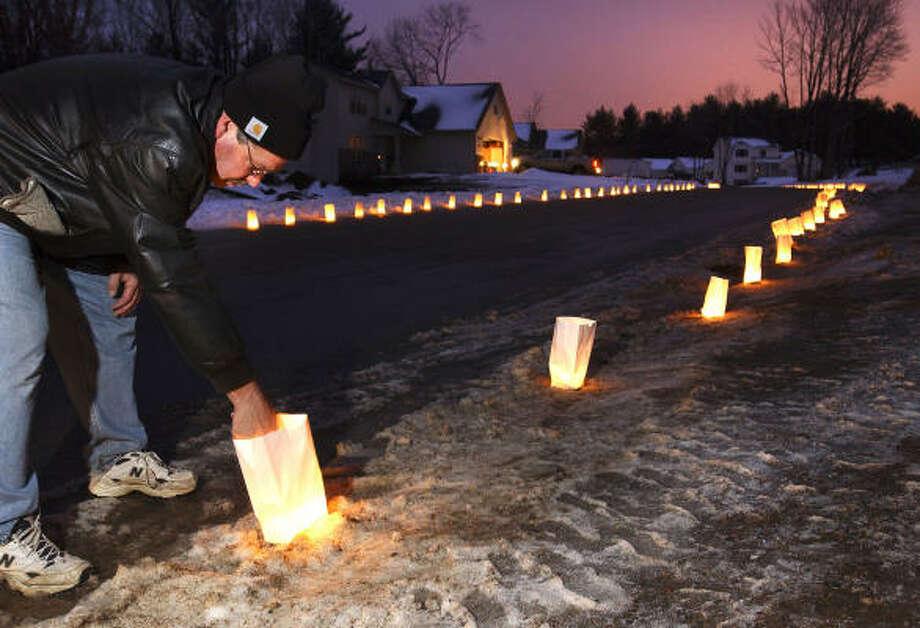 Jim Klapperich joins neighbors in lighting luminaries on Christmas Eve in Wausau, Wis. Photo: BUTCH MCCARTNEY, AP
