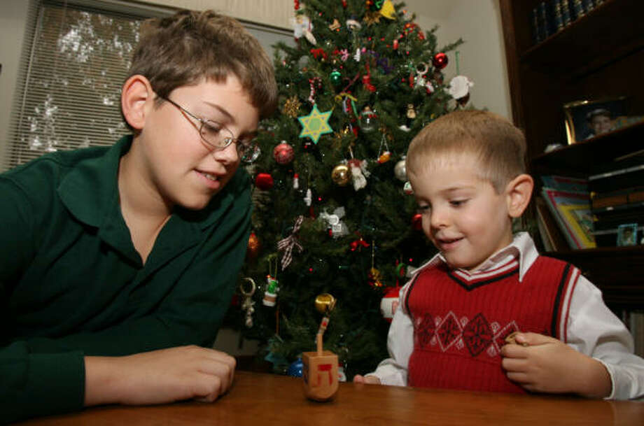 Twelve year-old David Williams and his five year-old brother Justin Williams play with a dreidel   in front of their family Christmas tree. David and Justin are part of a interfaith family. David is being raised Catholic like his mother; Justin is being raised Jewish, his father's faith. Photo: Billy Smith II