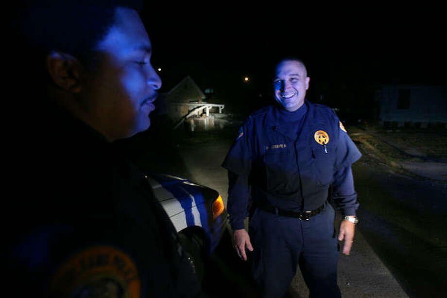 Officer Warren Walker, left, and  Lt. Billy Ceravolo, of New Orleans police's Fifth District, take a break during patroling of the Lower Ninth Ward at night. The police at night know who lives in the neighborhood, and can question people who are out after curfew to prevent looting. Photo: Mayra Beltran, Chronicle