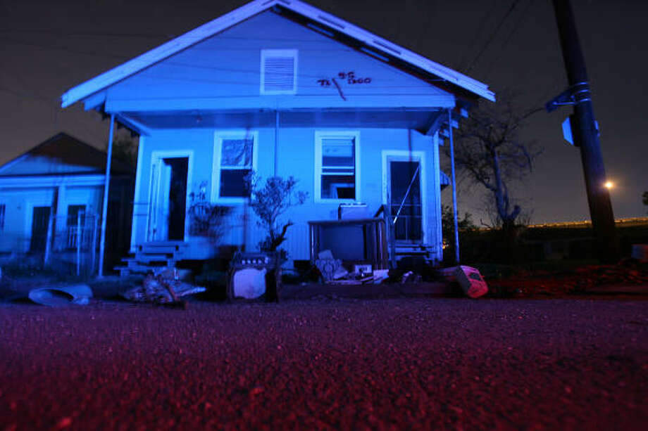 A damaged home in the Lower Ninth Ward of New Orleans is illuminated by police lights while officers patrol at night in late November. Photo: Mayra Beltran, Chronicle