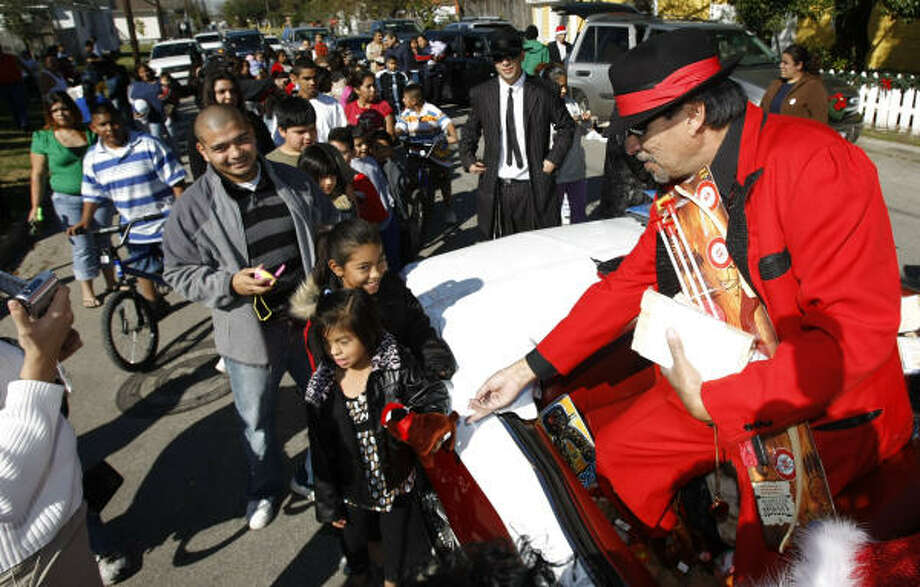 Pancho Claus delivers toys to children Tuesday in Houston. Pancho Claus, also known as Richard Reyes, annually delivers toys to children in this predominantly Hispanic neighborhood with the help of Precinct 6 deputy constables and the Latin Fantasy Car Club. Photo: Kevin Fujii, Chronicle
