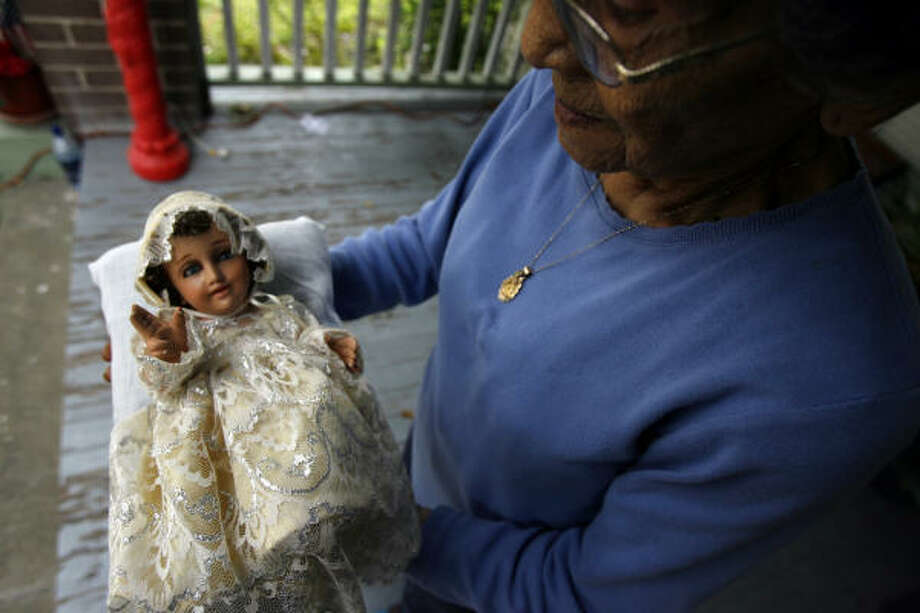 Mary Grace Rodriquez, 88, holds a porcelain baby Jesus she keeps in a nativity in her Houston home. The doll was given to her as a gift from Mexico, which she had blessed by a priest. Photo: Johnny Hanson, Chronicle