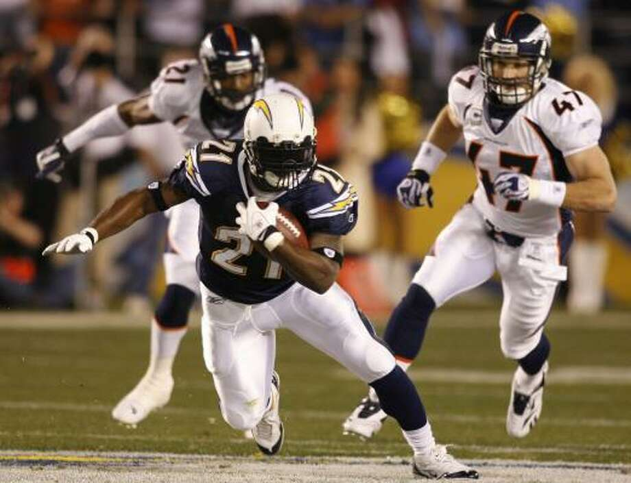 Chargers running back LaDainian Tomlinson (21) leaves Broncos' John Lynch, right, and Hamza Abdullah behind while running for a first down during the first quarter. San Diego went on to defeat Denver 23-3. Photo: Denis Poroy, AP