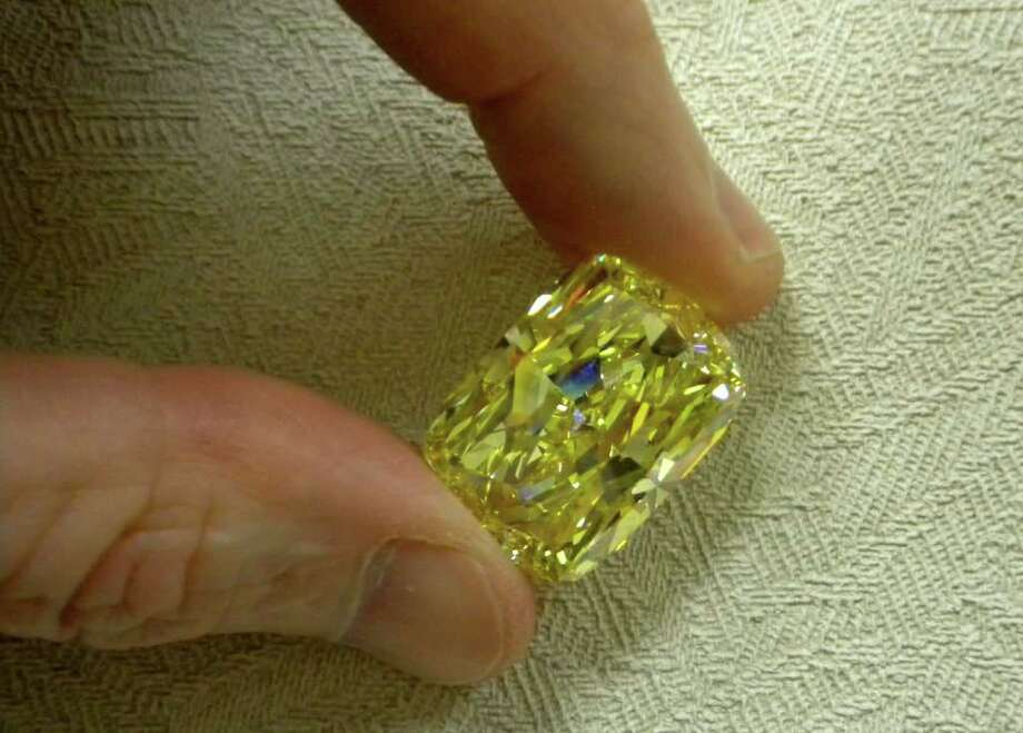 "This undated photo provided by the U.S. Marshals Service shows a large yellow diamond.  The large yellow diamond, known as the ""Golden Eye,"" was seized in a federal drug and money laundering investigation in northeast Ohio and is going on the auction block with the minimum bid to start at $900,000. The 43.51 carat diamond belonged to an Ohio businessman convicted of money laundering and conspiracy. A refundable deposit of $180,000 is required to be able to view the diamond in Cleveland the week of Aug. 29-Sept. 2 and bid on it during the auction that begins at 8 a.m. on Sept. 6 and continues until 3 p.m. Sept. 8. (AP Photo/U.S. Marshals Service)"