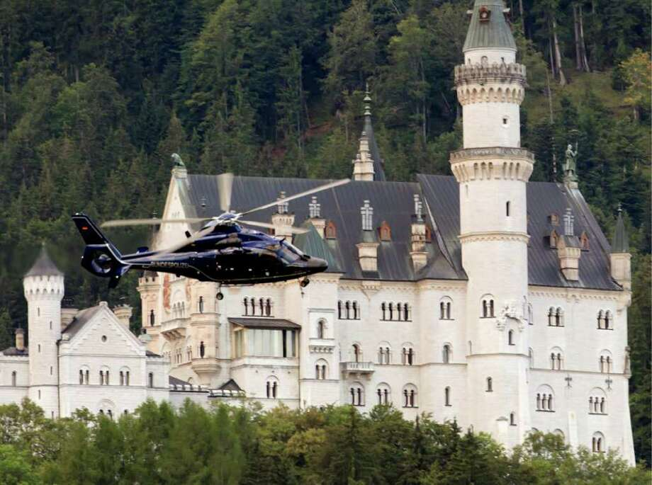 A helicopter of the German Federal  Police passes the famous Neuschwanstein Castle near Schwangau, Germany  Saturday Aug. 13, 2011. Authorities say 20 tourists who had been trapped overnight in a gondola in southern Germany's Alps could be safely freed.  Emergency service spokesman Roland Ampenberger says helicopter crews rescued the tourists, including several children, early Saturday morning after they had spent about 17 hours inside the gondola. Police say the gondola was blocked Friday after a paraglider crashed into the teleferic's cables, but strong winds hindered a swift rescue effort. Tegelberg mountain is within sight of one of Germany's popular tourist attractions, the Neuschwanstein Castle which is often viewed as the inspiration for one of Walt Disney's fairy tale castles. (AP Photo/dapd/Sebastian Widmann/dapd) Photo: Sebastian Widmann / dapd