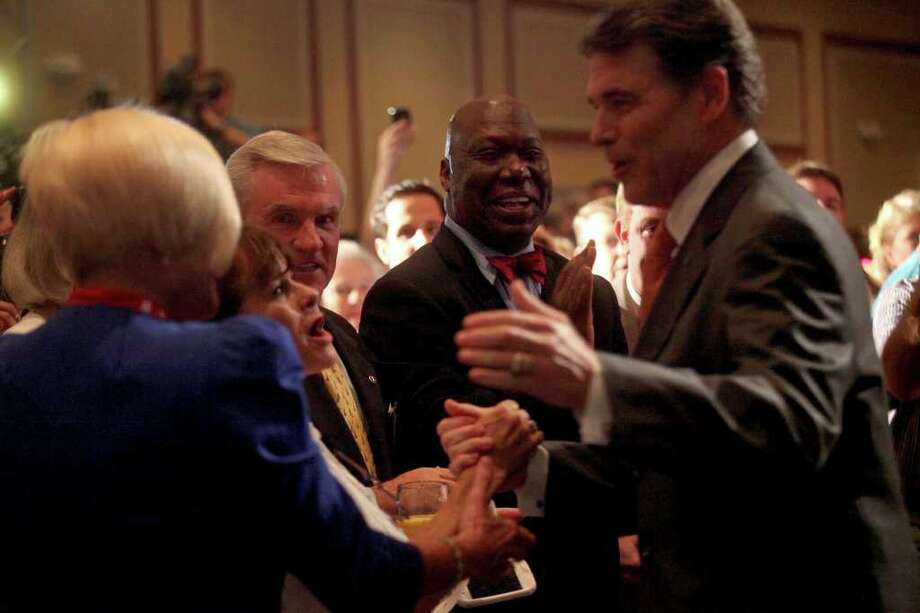 Michael Williams, former Chairman of the Railroad Commission of Texas and a candidate for U.S. Congress from Texas, center, watches as Governor Rick Perry greets supporters including Judy Crawford, of Atlanta, GA, left, upon entering the Carolina Ballroom to announce his run for President of the United States during the RedState Gathering at the Francis Marion Hotel in Charleston, SC on Saturday, August 13, 2011. Photo: LISA KRANTZ, LISA KRANTZ/lkrantz@express-news.net / SAN ANTONIO EXPRESS-NEWS