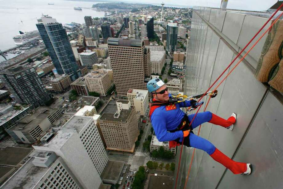 Craig Norris, dressed as Superman, begins his descent of Seattle's 41-story Rainier Square Tower during Over the Edge, a fundraiser for Special Olympics Washington, on Saturday, August 13, 2011 in Seattle. Nearly 200 people who raised money for Special Olympics Washington rappeled down the 514-foot tall building, which was built in 1977 and designed by Seattle native Minoru Yamasaki, who also designed the World Trade Center towers in New York. Photo: JOSHUA TRUJILLO / SEATTLEPI.COM