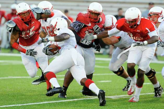 Lamar running back DePauldrick Garrett, left, picks up yardage against the defense during the Cardinals first preseason scrimmage at Provost Umphrey Stadium.  Saturday, August 13, 2011.  Valentino Mauricio/The Enterprise