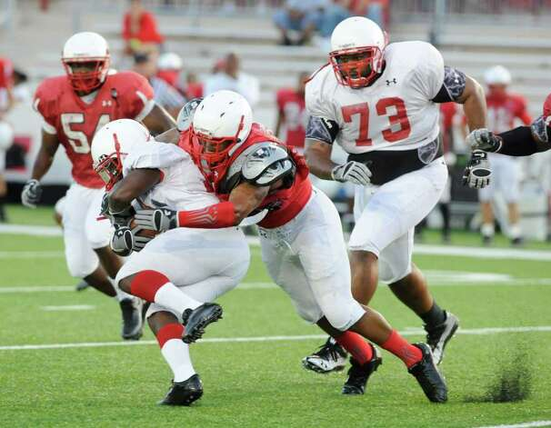Lamar running back DePauldrick Garrett, left, gets stopped by Jacody Coleman on defense during the Cardinals first preseason scrimmage at Provost Umphrey Stadium.  Saturday, August 13, 2011.  Valentino Mauricio/The Enterprise Photo: Valentino Mauricio