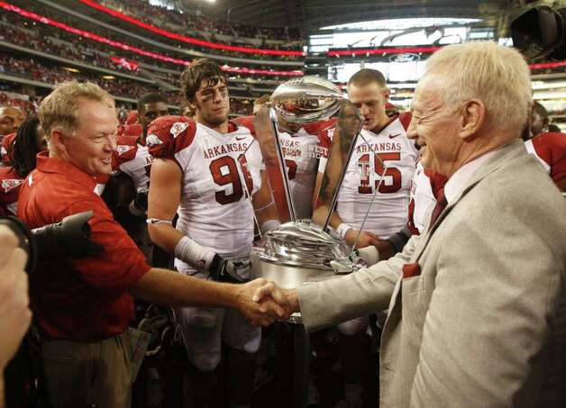 Arkansas head coach Bobby Petrino shakes hands with Dallas Cowboys owner Jerry Jones while presenting the Southwest Classic  trophy,  as Arkansas Razorbacks defensive end Jake Bequette (91) and quarterback Ryan Mallett (15) look on, after they defeated Texas A&M 24-17, during their NCAA football game at Cowboys Stadium in Arlington, Tx on October 09 2010. (Michael Ainsworth/The Dallas Morning News) Photo: MICHAEL AINSWORTH/Staff Photogra / Beaumont