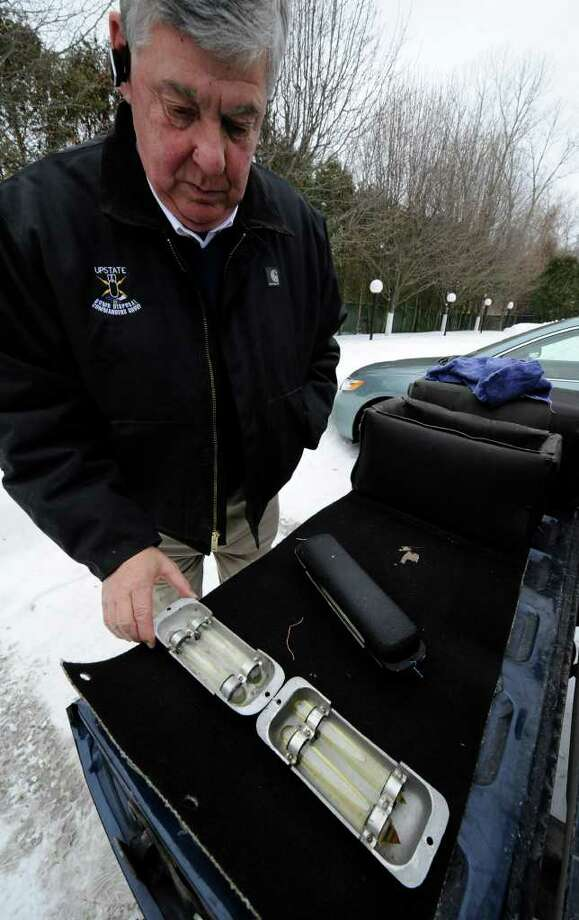 Albany County Sheriff's Department Inspector John Curry, a resident of Rensselaer County, looks at tubes of an unknown liquid in December 2010. Curry's job application with the department listed an address for an Albany County veterinarian's office when he was hired eight years ago. (Skip Dickstein / Times Union) Photo: Skip Dickstein