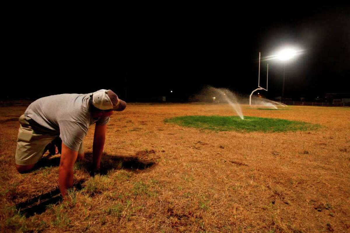 """School Superintendent and Athletic Director for Robert Lee High School, Aaron Hood, adjusts the underground sprinkler system that is providing the life support for the school's' dried football field, Wednesday, Aug. 10, 2011, in Robert Lee. The school waters the field nightly, putting on over 6,000 gallons a day costing $200 per load of water that is trucked in from a neighboring city. """"We take pride in our field, but it's also a matter of safety,"""" Hood said. """"Not only for out team but for other teams when they visit, they need a semi-soft spot to fall."""" The city of Robert Lee is experiencing an unprecedented drought receiving around 3 inches of rain in the past year. The city's drinking water is nearly dried up coming from the local Lake E.V. Spence which is at .7% capacity. Families have been forced to conserve water cutting back from 20,000 gallons per family per month to 3,000 to 4,000 gallons. If the city continues to receive no significant rain fall, the city will run out of water by early 2012. ( Michael Paulsen / Houston Chronicle )"""