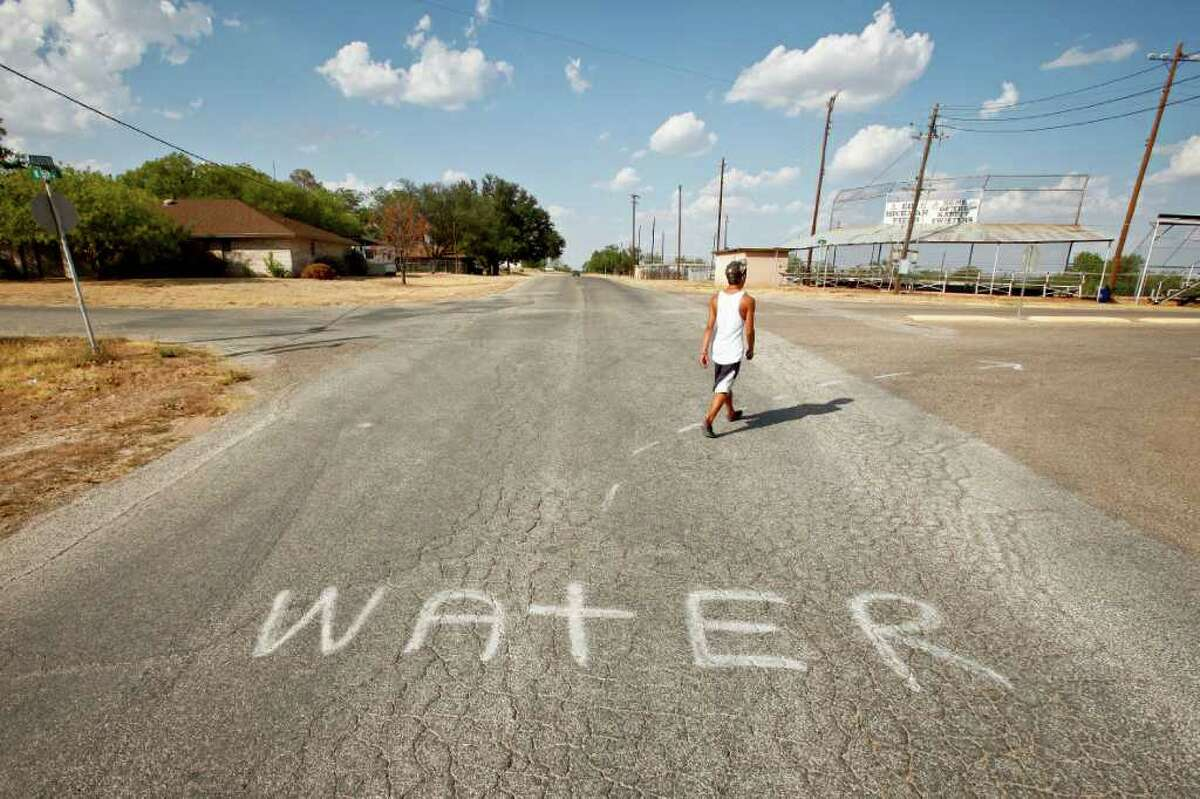 Jesus Landeros, 14, walks to the city pool and past a spray painted sign directing firefighters to a water source to fill their tankers while fighting the recent Wildcat Fire that threatened the town and burnt 160,000 acres, Wednesday, Aug. 10, 2011, in Robert Lee. The city's pool was recently used by a firefighting helicopter when it scooped several hundred gallons to be dropped on a nearby wildfire that threatened the town and burnt 160,000 acres. The city of Robert Lee is experiencing an unprecedented drought receiving around 3 inches of rain in the past year. The city's drinking water is nearly dried up coming from the local Lake E.V. Spence which is at .7% capacity. Families have been forced to conserve water cutting back from 20,000 gallons per family per month to 3,000 to 4,000 gallons. If the city continues to receive no significant rain fall, the city will run out of water by early 2012. ( Michael Paulsen / Houston Chronicle )