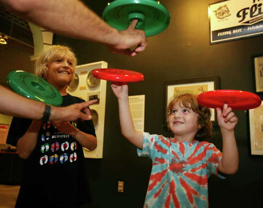 Brothers Jacob, 9, and Jesse Deck, 5 of Fairfield, spin frisbees on their fingers at the opening of the Bridgeport: First in Flight exhibit at the Discovery Museum in Bridgeport on Sunday, August 14, 2011. The exhibit celebrates the 110th anniversary of Gustave Whitehead's first flight, Igor Sikorsky, and the frisbee, which originated as a pie plate at the Frisbee Baking Company on Kossuth Street in Bridgeport. Photo: Brian A. Pounds / Connecticut Post
