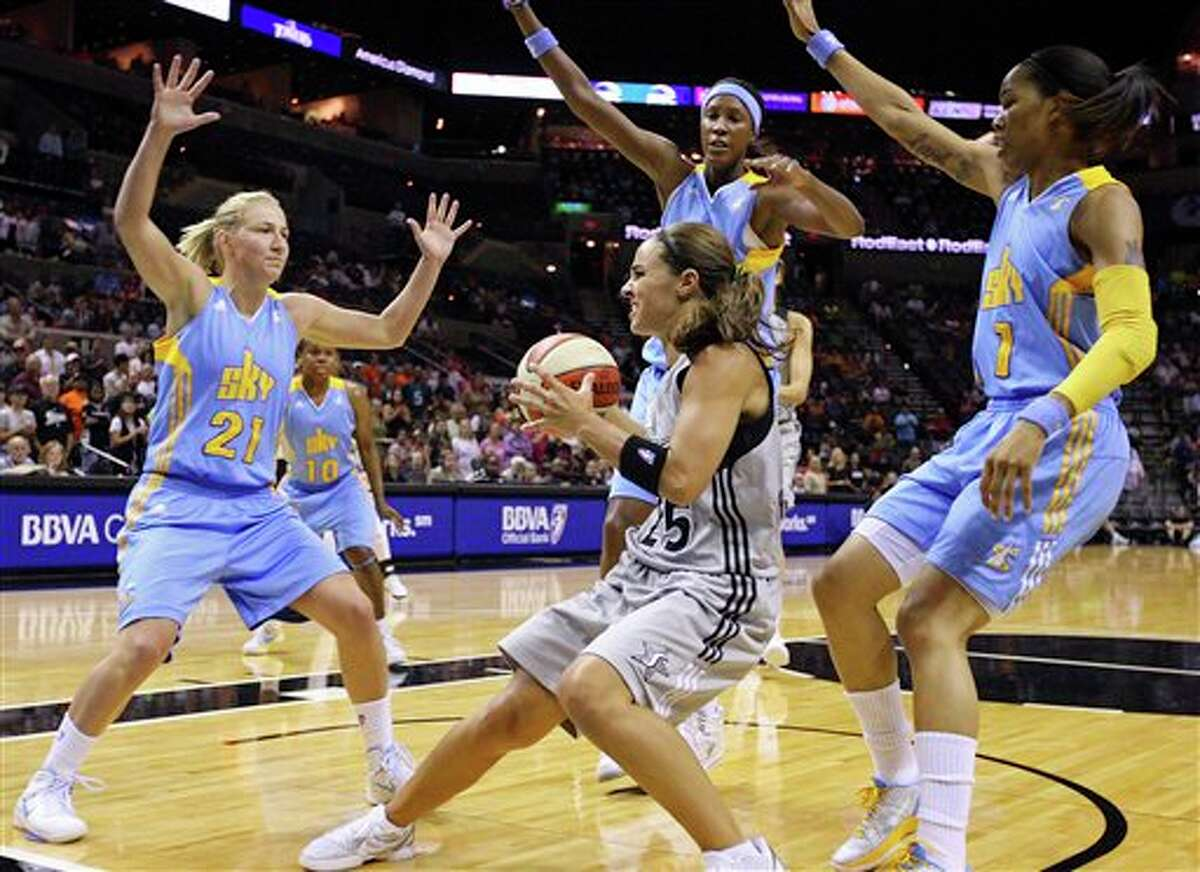 The Silver Stars' Becky Hammon looks for room between Chicago Sky's Courtney Vandersloot ( from left), Michelle Snow and Tamera Young during the first half at the AT&T Center on Sunday.