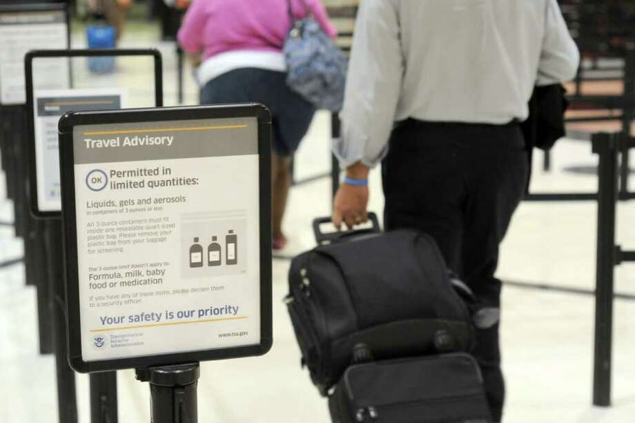In this Aug. 3, 2011 photo, an airline passenger wheels a carry-on bag up to the Transportation Security Administration security checkpoint at Hartsfield-Jackson Atlanta International Airport, in Atlanta. Photo: Erik S. Lesser, FRE / FR53108 AP