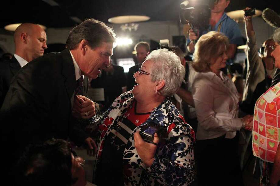 Metro - Linda Love of Cedar Falls, IA, greets Governor Rick Perry as he arrives for The Black Hawk County Lincoln Day Dinner in the Electric Park Ballroom at the National Cattle Congress in Waterloo, Iowa on Sunday, August 14, 2011. LISA KRANTZ/lkrantz@express-news.net / SAN ANTONIO EXPRESS-NEWS