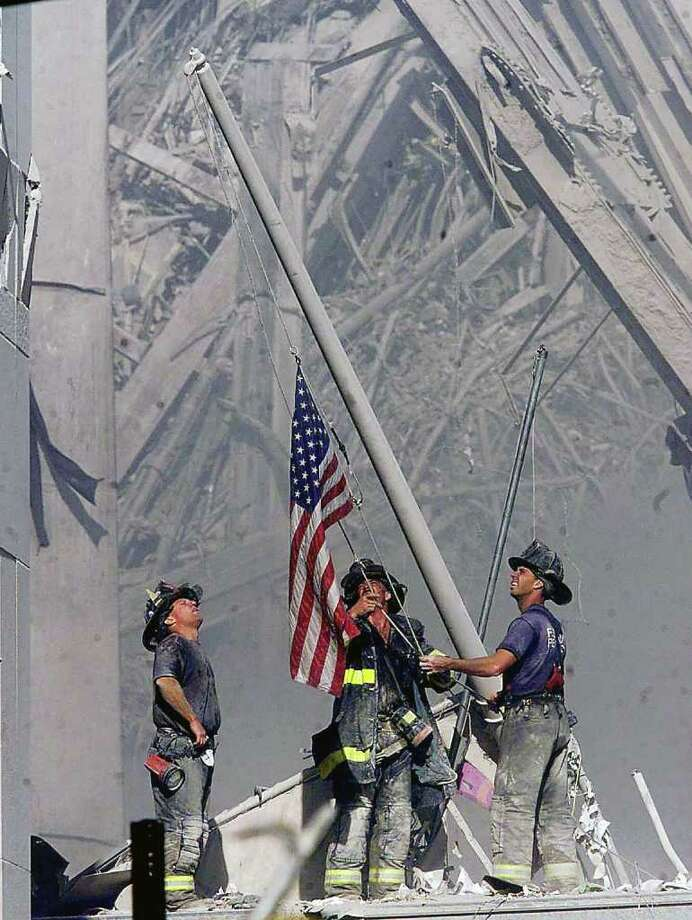 ** FOR USE AS DESIRED WITH SEPT. 11 ANNIVERSARY STORIES--FILE **Brooklyn firefighters George Johnson, left, of ladder 157, Dan McWilliams, center, of ladder 157, and Billy Eisengrein, right, of Rescue 2, raise a flag at the World Trade Center in New York, in this Sept. 11, 2001, file photo, as work at the site continues after hijackers crashed two airliners into the center. In the most devastating terrorist onslaught ever waged against the United States, knife-wielding hijackers crashed two airliners into the World Trade Center, toppling its twin 110-story towers. This year will mark the fifth anniversary of the attacks.  (AP Photo/ Copyright 2001 The Record (Bergen County, NJ), Thomas E. Franklin, Staff Photographer/FILE) MANDATORY CREDIT NO SALES ONLINE OUT Photo: THOMAS E. FRANKLIN / j=adv_sep11_wirephotos