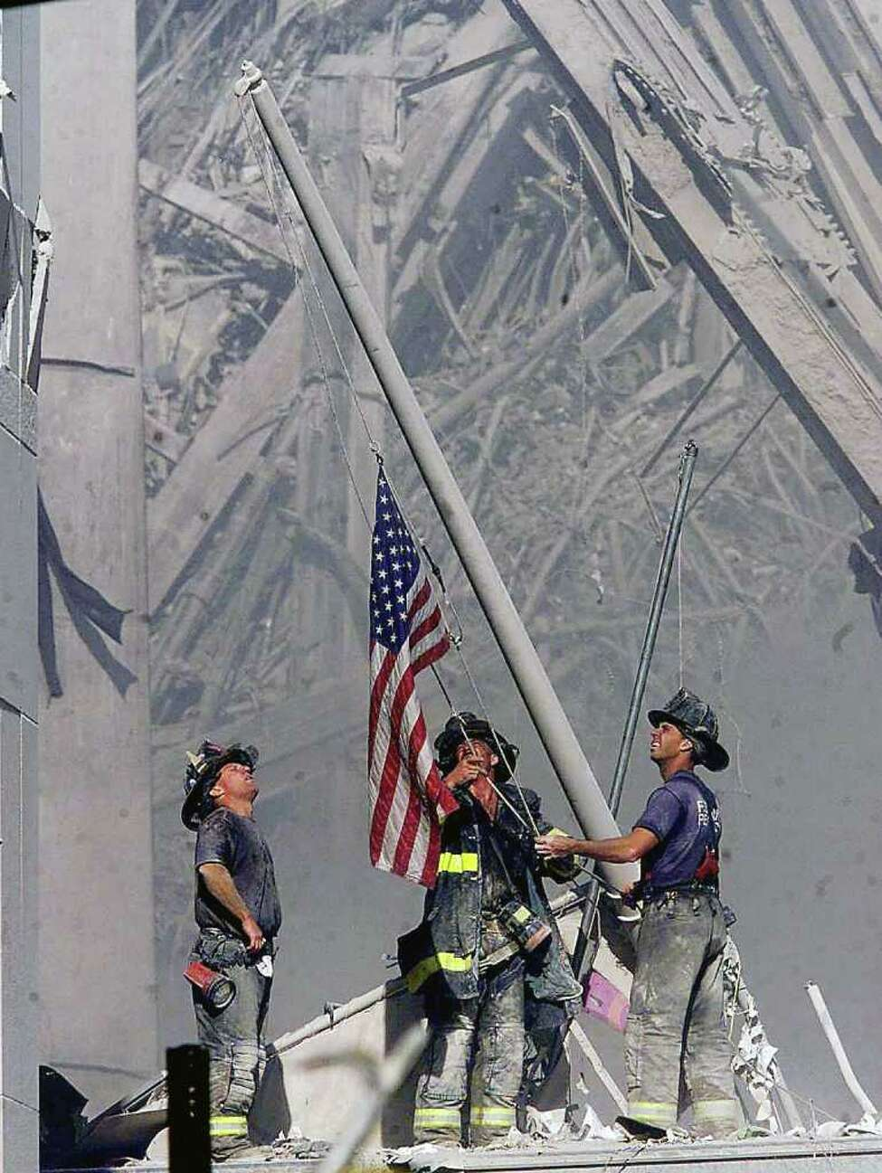 Brooklyn firefighters George Johnson, left, of ladder 157, Dan McWilliams, center, of ladder 157, and Billy Eisengrein, right, of Rescue 2, raise a flag at the World Trade Center in New York, in this Sept. 11, 2001, file photo, as work at the site continues after hijackers crashed two airliners into the center.