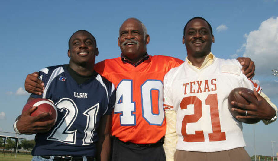 Grady Cavness Jr., in a Texas jersey, stands with his father Grady Cavness Sr., (center) in a Denver Broncos jersey, and Trevor Cavness of Elsik High School. Photo: Gary Fountain, For The Chronicle