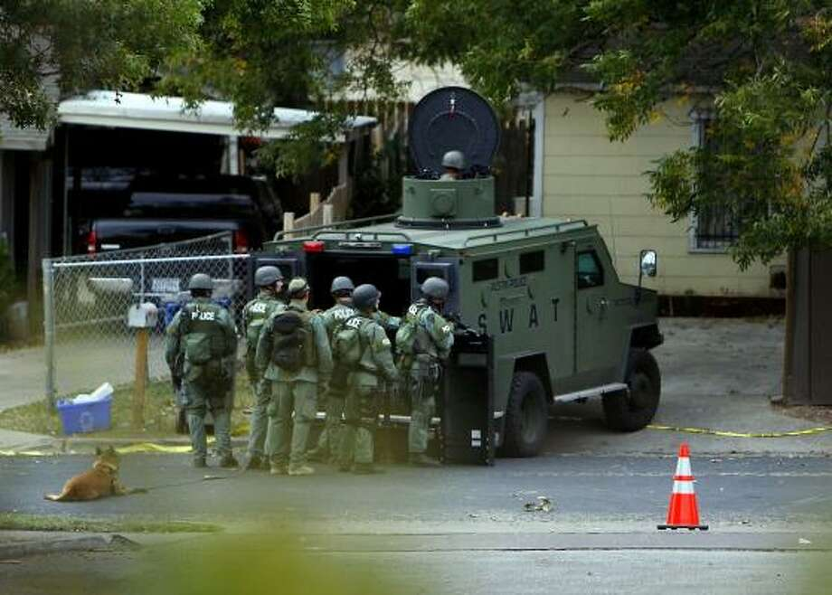 Police gather near a northeast Austin home Thursday morning during a search for robbery suspects. The search forced Austin school district officials to close some schools. Photo: RICARDO B. BRAZZIELL, AUSTIN AMERICAN-STATESMAN