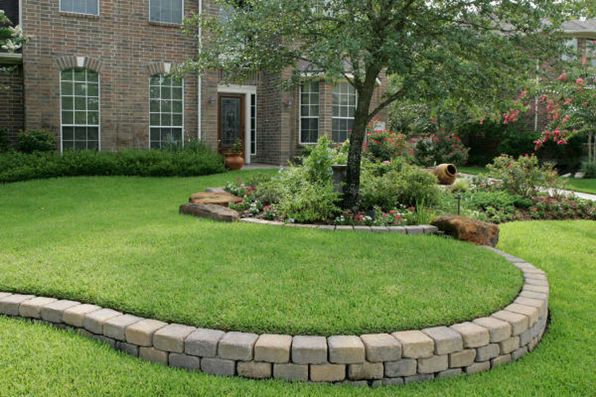 A curving retaining wall of tumbled concrete blocks snakes across a terraced St. Augustine lawn in Spring.