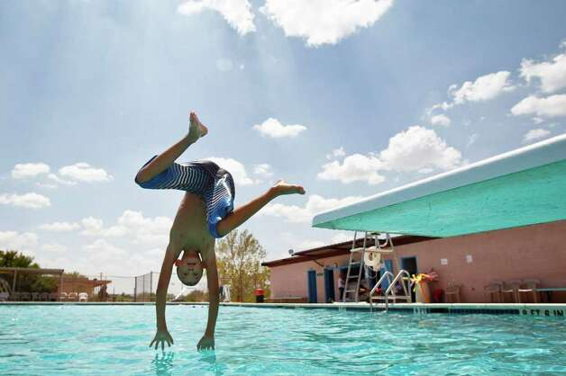 Trace Oleksiuk, 12, jumps into the Robert Lee city pool as the temperature toped out at 110 degrees, Wednesday, Aug. 10, 2011. The city's pool was recently used by a firefighting helicopter when it scooped several hundred gallons to be dropped on a nearby wildfire that threatened the town and burnt 160,000 acres. Photo: Michael Paulsen, Michael Paulsen/Houston Chronicle / © 2011 Houston Chronicle