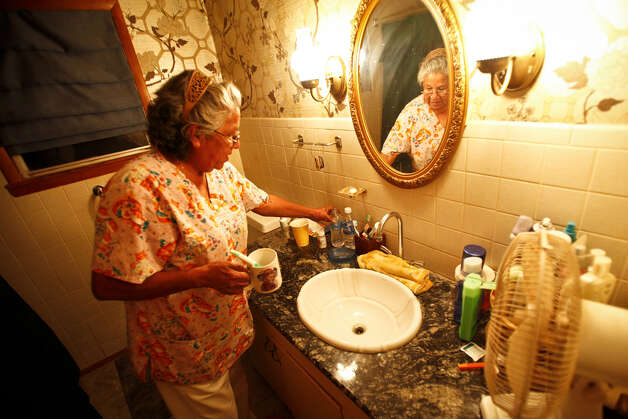 Lori Sevier grabs a bottled water to brush her teeth at her home as she refuses to use the salty cloudy city water with a foul smell, Wednesday, Aug. 10, 2011, in Robert Lee. Photo: Michael Paulsen/Houston Chronicle