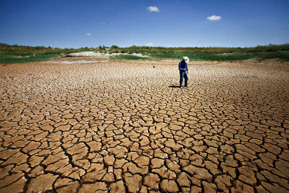 """County Extension Agent, Garrett Gilliam, walks through a sun-scorched cracked lake bed where at one time an estimated 30-feet of water once stood at Lake E.V. Spence, Wednesday, Aug. 10, 2011, in Robert Lee.  """"The morale is to survive,"""" Gilliam said. """"The good times will come again and we just keep praying to the good Lord that he'll bless us."""""""