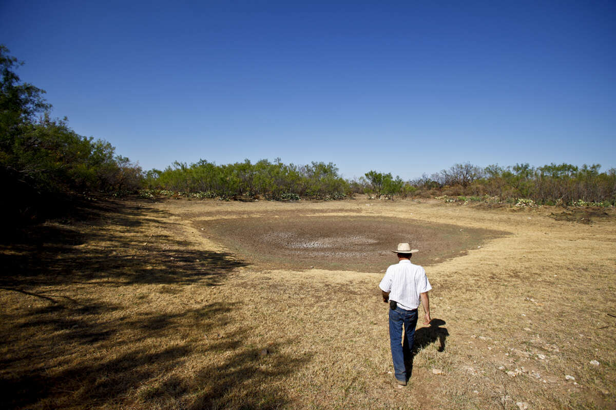 Bobby Blaylock, County Commisioner and rancher, walks down to his sun-scorched watering tank he used to use for livestock on his ranch, Wednesday, Aug. 10, 2011, in Robert Lee. Blaylock and his sons grew up fishing in the tank,