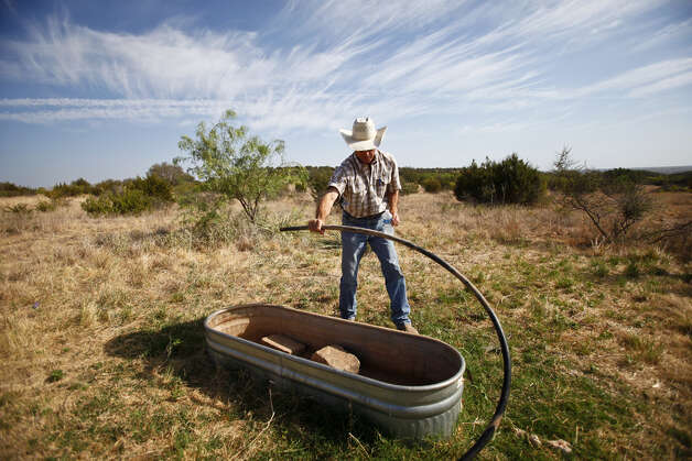 Rancher, Lee Hortenstine, checks a water trough on his ranch as the temperature toped out at 110 degrees, Wednesday, Aug. 10, 2011, in Robert Lee.  The city of Robert Lee is experiencing an unprecedented drought receiving around 3 inches of rain in the past year. The city's drinking water is nearly dried up coming from the local Lake E.V. Spence which is at .7% capacity. Families have been forced to conserve water cutting back from 20,000 gallons per family per month to 3,000 to 4,000 gallons. If the city continues to receive no significant rain fall, the city will run out of water by early 2012. Photo: Michael Paulsen/Houston Chronicle