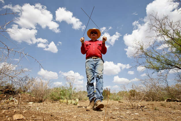 "Bobby Blaylock, County Commisioner and rancher, uses dowsing rods to look for water on his ranch, Wednesday, Aug. 10, 2011, in Robert Lee. Currenlty, Blaylock has a decent well that his father dug years ago that provides enough water for his family and livestock, but he has practiced water-witching for many years in case he needs to red rill. ""I have no explanation as to why it works,"" Blaylock said. ""They just cross for some people."" Photo: Michael Paulsen/Houston Chronicle"